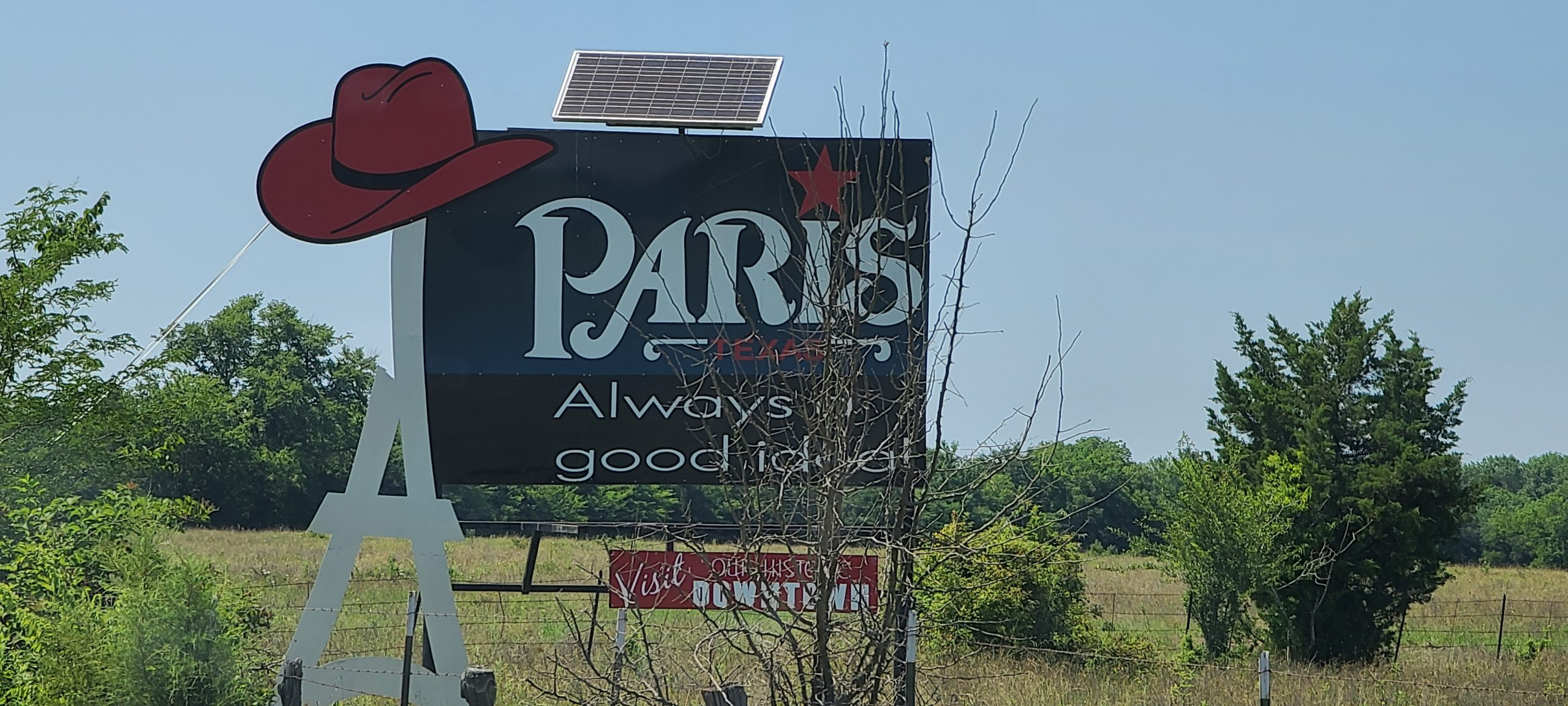Paris, Texas signpost on entering city with the Eiffel Tower and a red cowboy on its top
